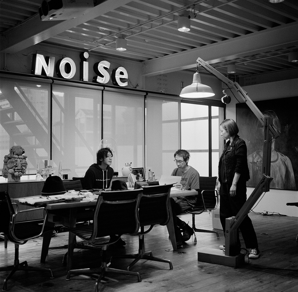 アンダーカバーのコンセプトは『We make noise not clothes(服ではなくノイズを作る)』。高橋のオフィスにある赤と白のネオンサインは、この理想を表したものだ。東京・原宿の裏通りにある、黒い鉄箱が浮いているように見える建物が彼のアトリエだ。最上階は高橋の仕事部屋。そこで高橋はデザインや、できあがった商品の最終チェックを行う。写真は、高橋とメンズラインであるジョンアンダーカバーのデザイナーたちのミーティング風景。高橋の左手側に立つのは、彼の右腕として知られる女性