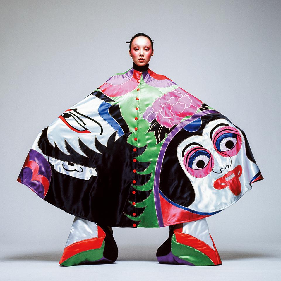奴(やっこ)の隈取りが描かれた ケープを着たモデルのマリー。  奴は、戯画化された姿で歌舞伎の舞台によく登場する。  しかし、色使いは典型的な70年代のグラムロックテイストだ  © HIROSHI YODA