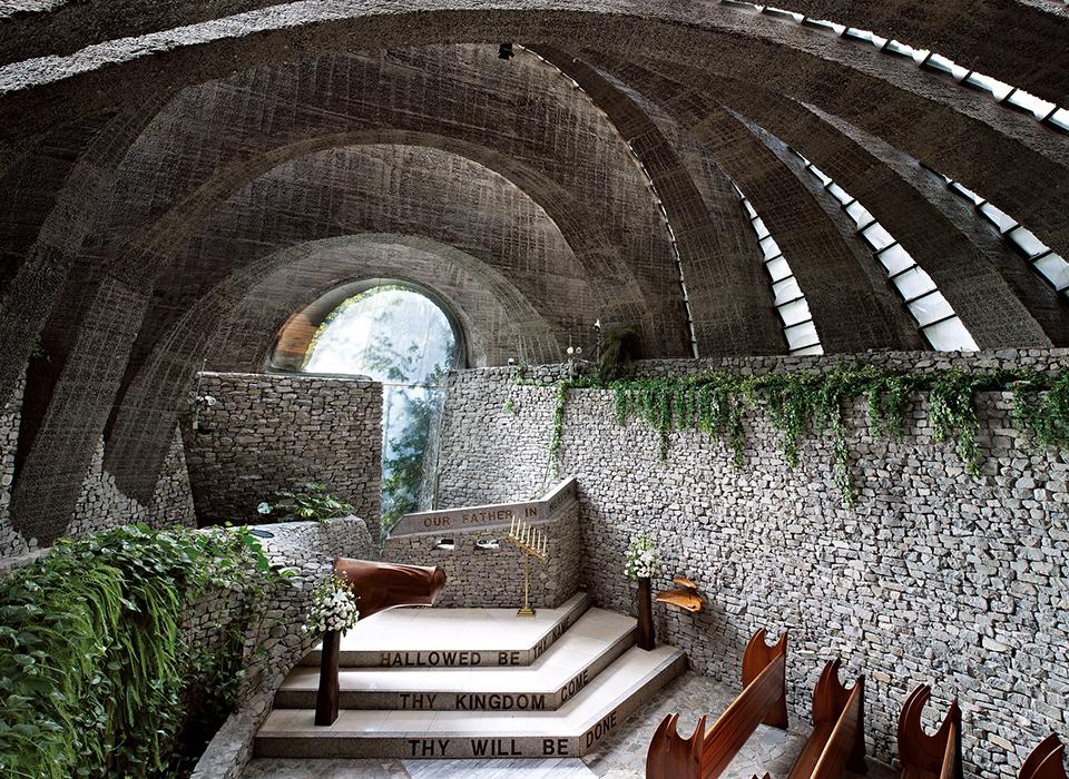 コンクリートのアーチがドミノ倒しのように傾いて連なり、垂直なアーチはひとつもない。 中に入ると石を積み上げた壁で囲まれた荘厳な世界が広がる