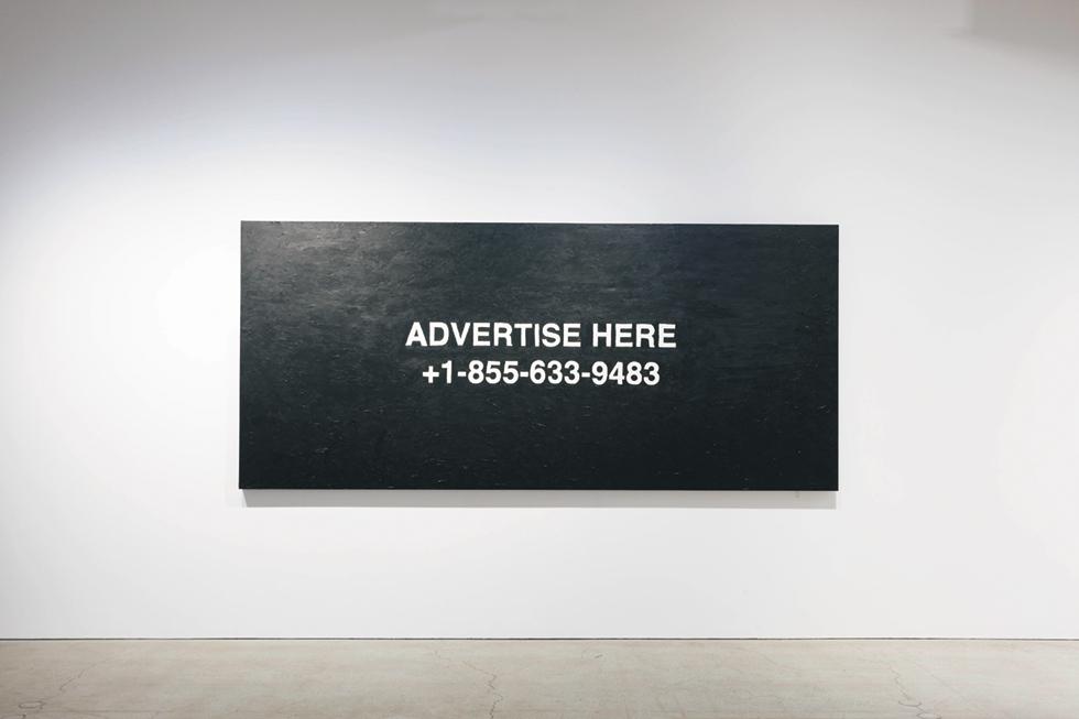 """3月に東京で行われた初個展『""""PAY PER VIEW""""』。  《""""advertise here""""》(2018, Oil on canvas 3200 × 1430mm)  と題された作品には、  ヴァージルの昔の携帯番号と留守録のメッセージが描かれている  PHOTOGRAPH BY KOICHIRO MATSUI"""