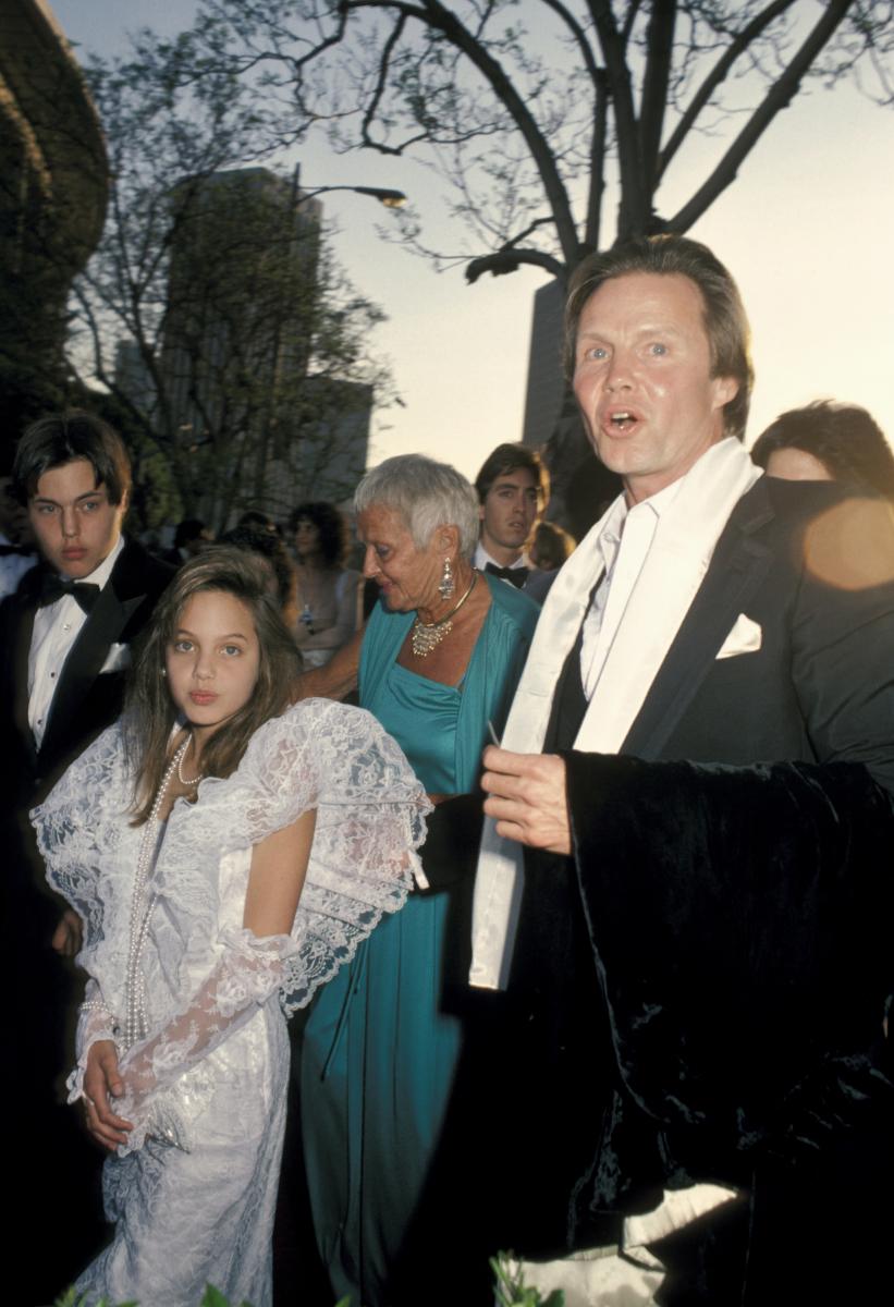 1986年の第58回アカデミー賞授賞式に父ジョン(右)に連れられ出席した、セレブキッズ時代のアンジー。白いレースのドレスは子どもらしいけれど、表情は10歳とは思えない大人っぽさ! この時すでに父の主演作『大狂乱』(1982)で子役デビュー済み。