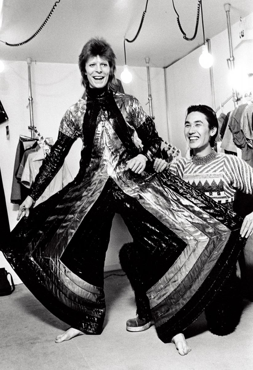 『ジギー・スターダスト』ツアーで来日したデヴィッド・ボウイと山本寛斎。 寛斎のスタジオにて、1973年4月に撮影。 ボウイが着ているのは、寛斎の制作した 「スペース・サムライ」とでも呼びたいジャンプスーツ。 日本の伝統的な紳士用着物である袴をベースにしてデザインしたものだ © MASAYOSHI SUKITA
