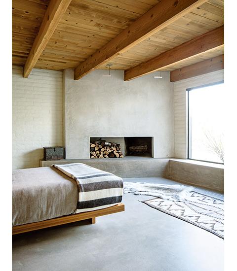 地元の家具職人ネイト・ダンフォースが、この家のすべての棚と、 主寝室のチーク材のベッドを作った。 暖炉の壁はしっくい、床に置かれた毛皮はトナカイ。 ナバホ族の手織りの絨毯は1920年代のものだ。 マットな風合いに磨かれたニッケル製の照明は、 ポール・ルドルフのデザインによる、モジュライター社製