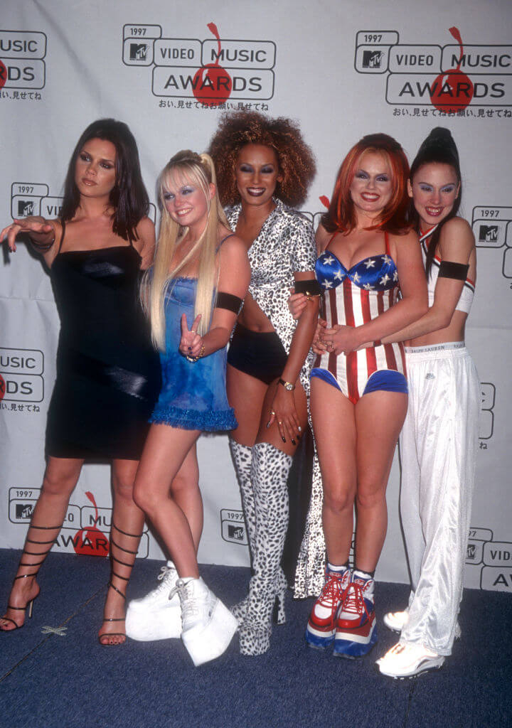 1994年、ジェリ・ハリウェル、エマ・バントン、メラニー・チズム、メラニー・ブラウンの4人とともにアイドルグループ「スパイス・ガールズ」を結成したヴィクトリア・ベッカム。