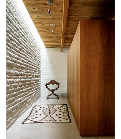 地平線 スコット・パスクのツーソンの自宅には、ぱっと目を引く劇場のセットのような仕掛けが施されている。たとえばこのヴィンテージのナバホ族の絨毯と、アンティークのサヴォナローラ・チェア(X型をした木製の折りたたみ椅子)が、白いモルタル加工のブロック壁とチーク材の壁に囲まれている光景が一例だ。床はコンクリートで固められている