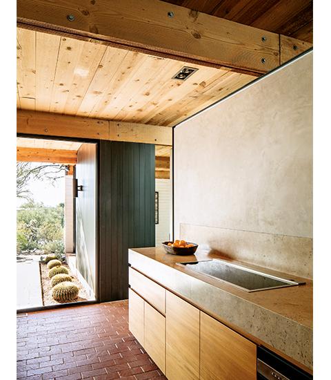 キッチンの床は、もともと使われていたレンガに再仕上げを施した。 カウンタートップにパスクが選んだのは、磨き抜かれたメキシコ産のトラバーチン。 貯蔵庫の棚は、濃い色の羽目板のドアの後ろに隠されている。 コンロはドイツのキッチン器具メーカー、ガゲナウのもので、 キャビネットにはチーク材を使用