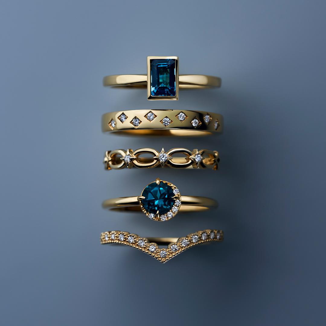 """(上から)""""スタッキング リング""""〈K18YG、ロンドンブルートパーズ〉¥42,000、〈K18YG ダイヤモンド〉¥65,000、〈K10YG、ダイヤモンド〉¥28,000、〈K18YG、ロンドンブルートパーズ、ダイヤモンド〉¥47,000、〈K18YG、ダイヤモンド〉¥55,000"""