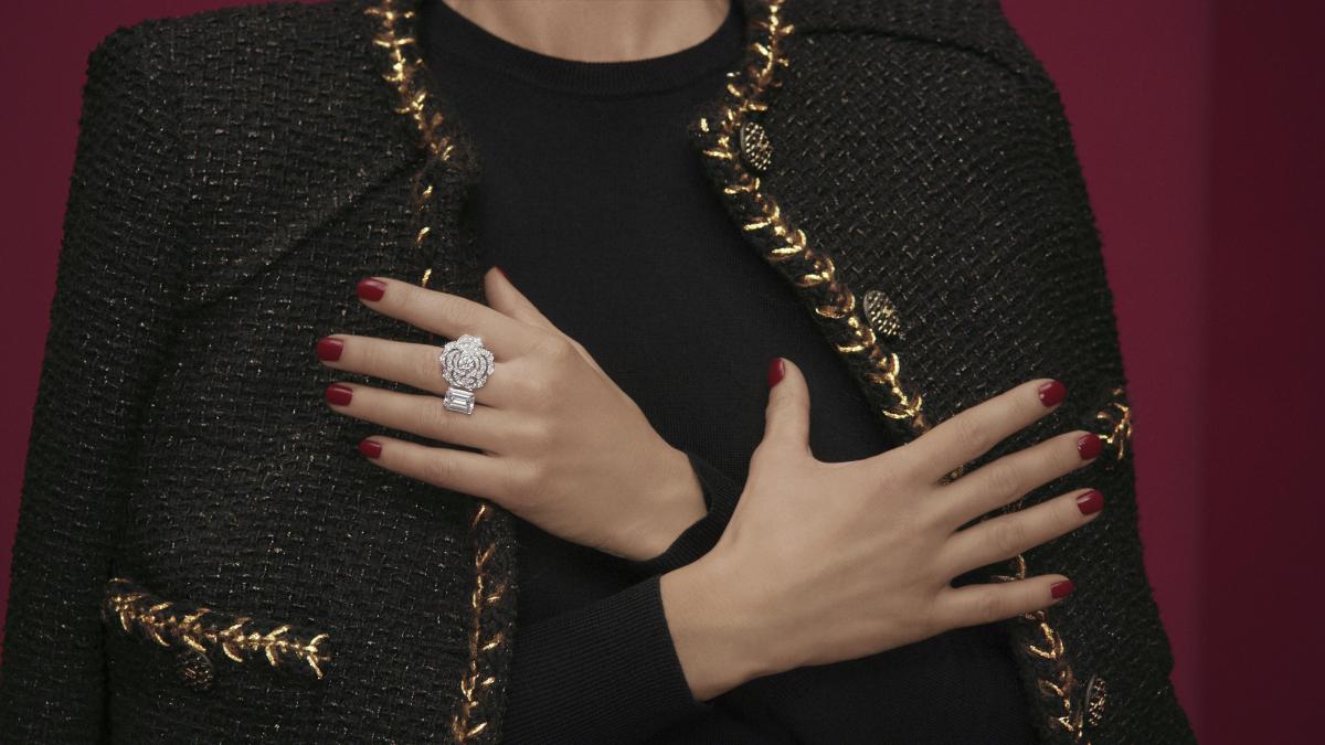 カメリアのモチーフと、5カラットのエメラルドカットダイヤモンドが左右から指を包み込むデザインのリング。