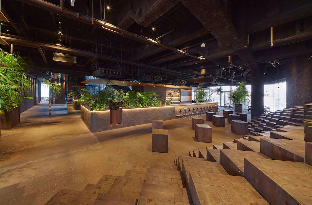 床や壁面、テーブルや椅子に土を使った、これまでにない空間。手前はイベントスペースにもなる自由な階段席。