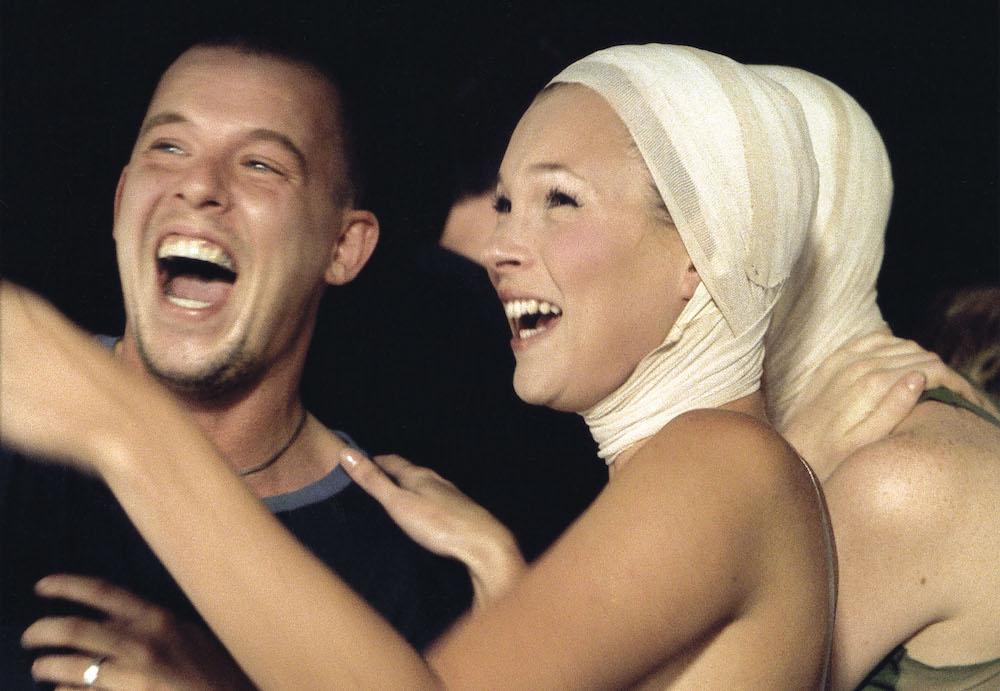 アレキサンダー・マックイーンの2001春夏ショー「Voss」のバックステージで、頭に包帯を巻いたケイト・モスと笑顔を見せるマックイーン。