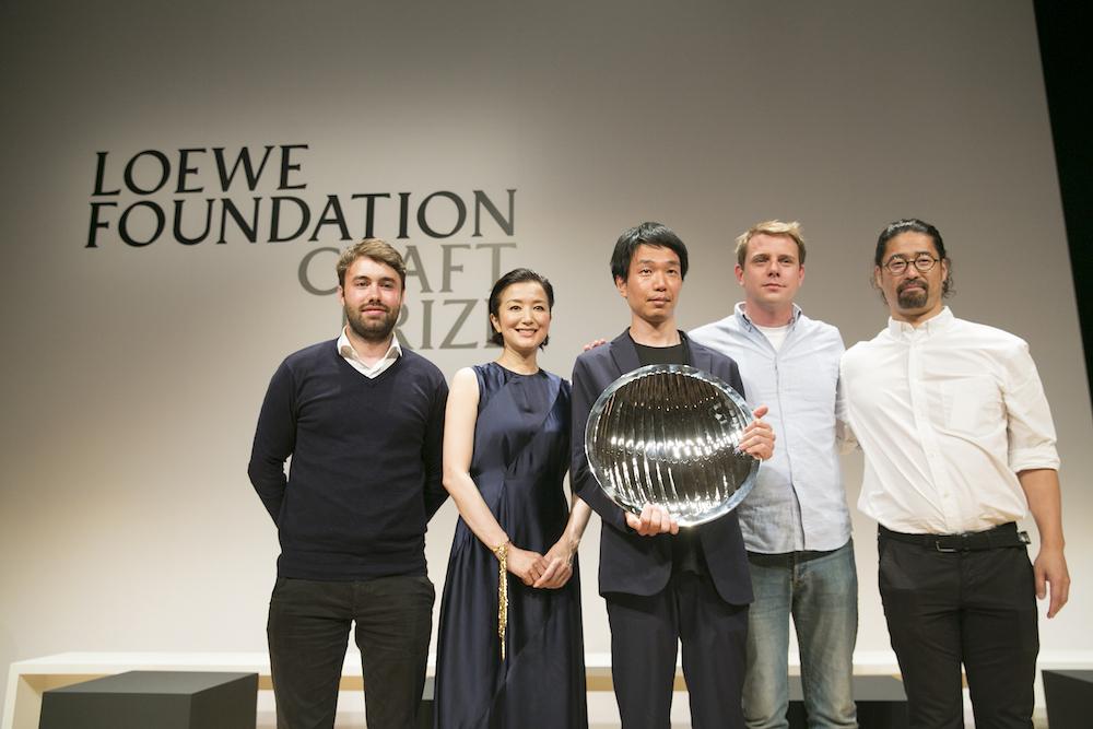 授賞式の壇上で喜びを分かち合う受賞者たち。左から特別賞のハリー・モーガン、グランプリのプレゼンターとして登場した鈴木京香、グランプリを受賞した石塚源太、ロエベのクリエイティブ ディレクターでこの賞の発案者であるジョナサン・アンダーソン、特別賞の高樋一人。石塚が手にしているのはイギリスの銀細工師、アレックス・ブログデンによるトロフィー。