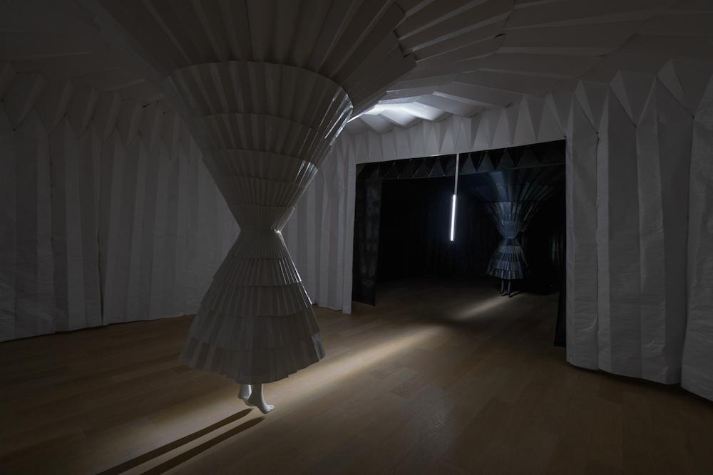 白と黒でくっきり分かれた空間に、プリーツスカートの襞が広がる。空間を満たすコンセプチュアルな音楽も、不思議な違和感を増幅。
