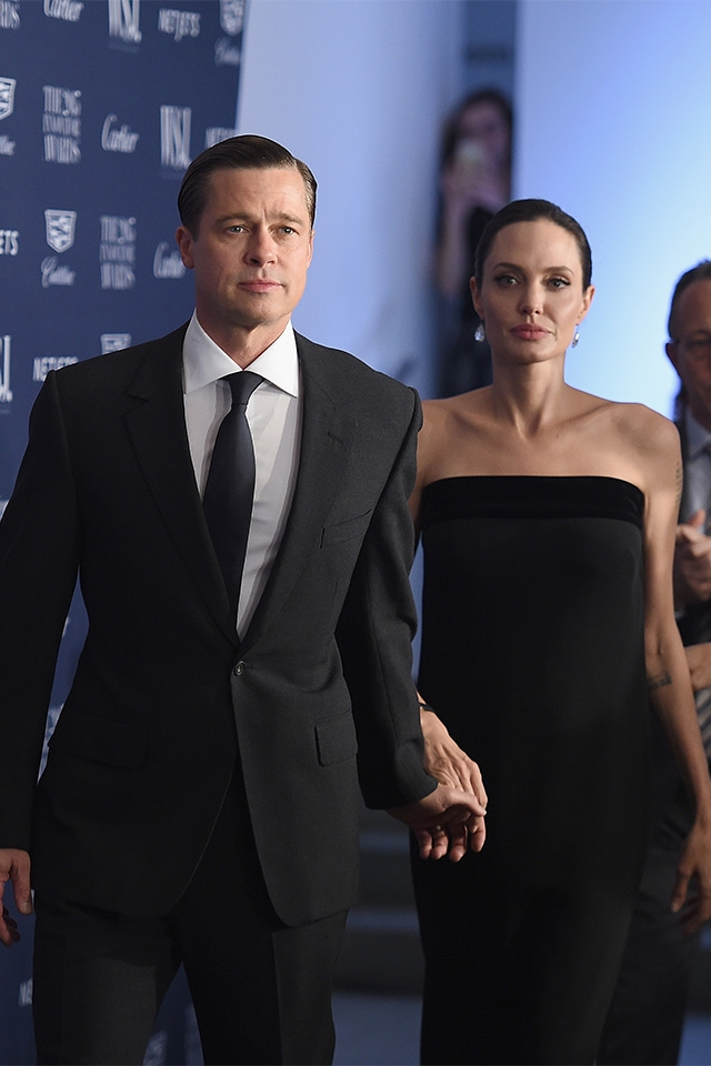 ハンツマンのオーダーメイドスーツにオールバックヘアのシックなスタイルで、トム・フォードのブラックドレスをまとったアンジーをエスコート