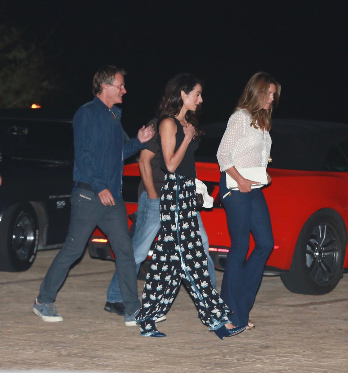 夫や友達とナイトアウトを満喫中。そんな楽しい夜は、スワンモチーフのステラ マッカートニーのパジャマパンツを選ぶあたりがさすが。それよりもさすが! なのは、隣に並ぶ友達がシンディ・クロフォードであるということ。元祖スーパーモデルと並んでこ絵になる一般人、それがアマル。