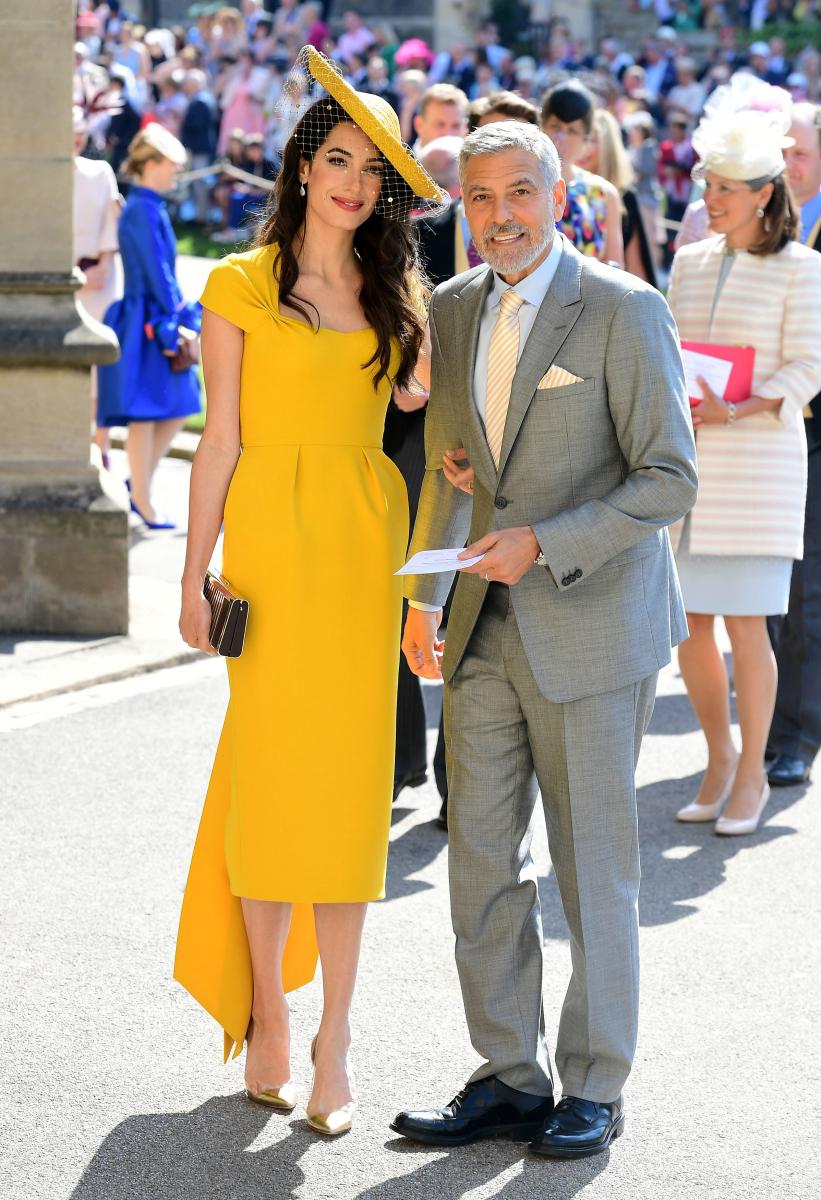 2018年5月、世界中が熱視線を送った、ヘンリー英王子とメーガン妃の結婚式に出席。ステラ マッカートニーの目が覚めるようなイエローの膝下丈ドレスに身を包んだアマルの美しさは、群を抜いていた。目立つ原色ながら、控えめの装飾とエレガントなフォルム、この日もアマルは完璧だった。