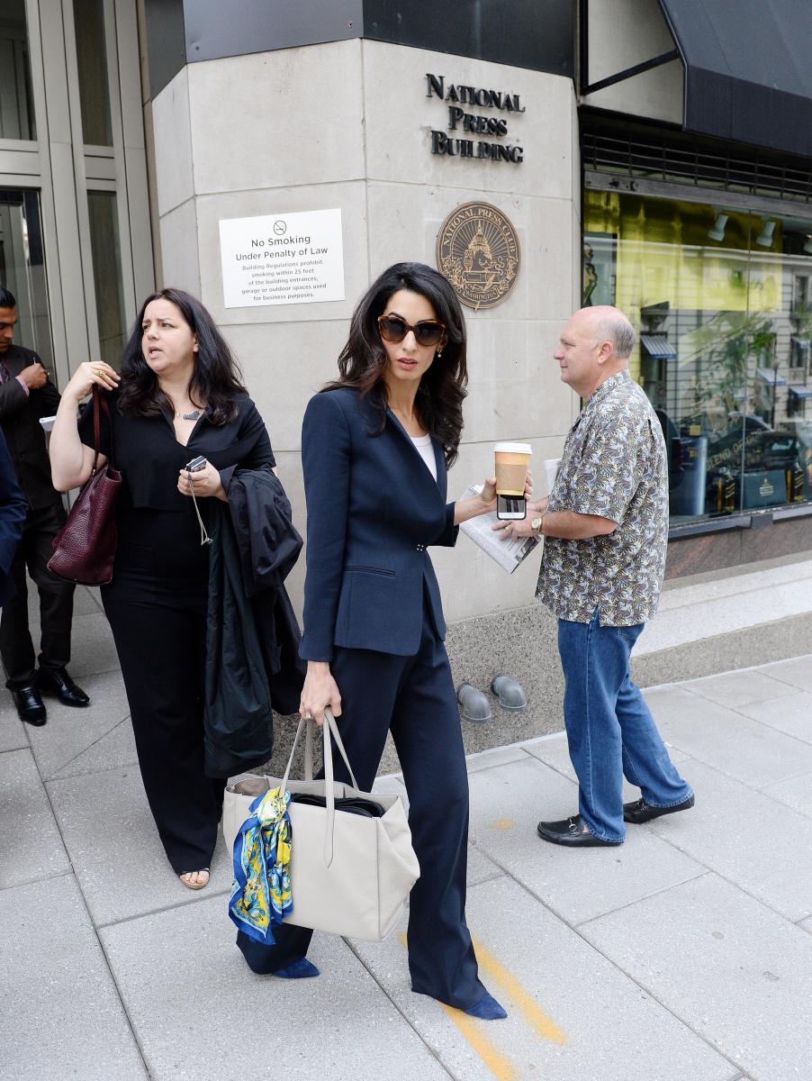 2015年4月、ワシントンの記者クラブを出るアマルは、珍しくシャープなパンツスーツ。ウエストをぎゅっと絞ったスーツの色合いに合わせ、スエードのポインテッドトゥシューズとバッグに巻いたスカーフもブルー。