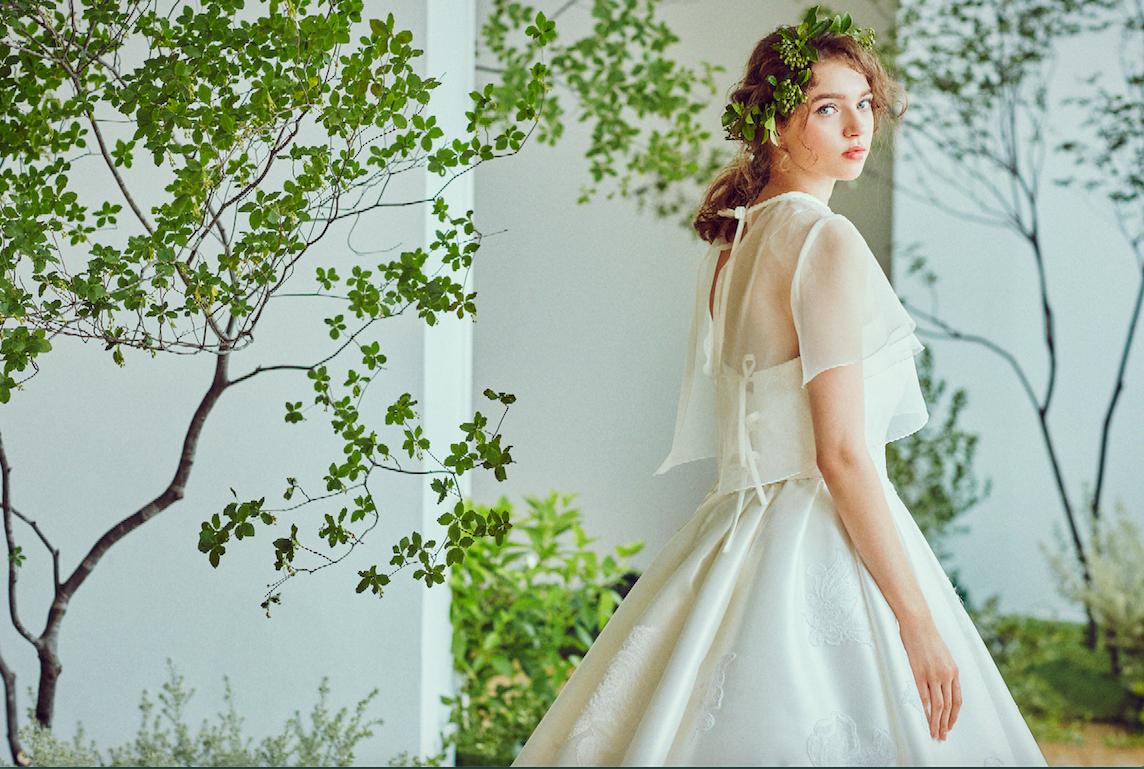 オーガンジーの柔らかなブラウスが透明感漂う一着。スカートの繊細なレース刺繍がエレガンスを感じさせる。