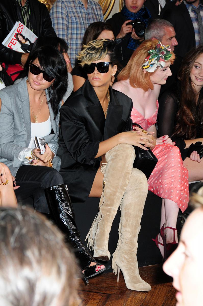 2009年ヴィヴィアン・ウエストウッドの春夏コレクションのフロントロウにて。デビューから4年後ながら、ただならぬ大物感を放つようになったリアーナ。サテンのビッグジャケットにフリンジ付きサイハイブーツを合わせ、レンズの大きなサングラスをオン。