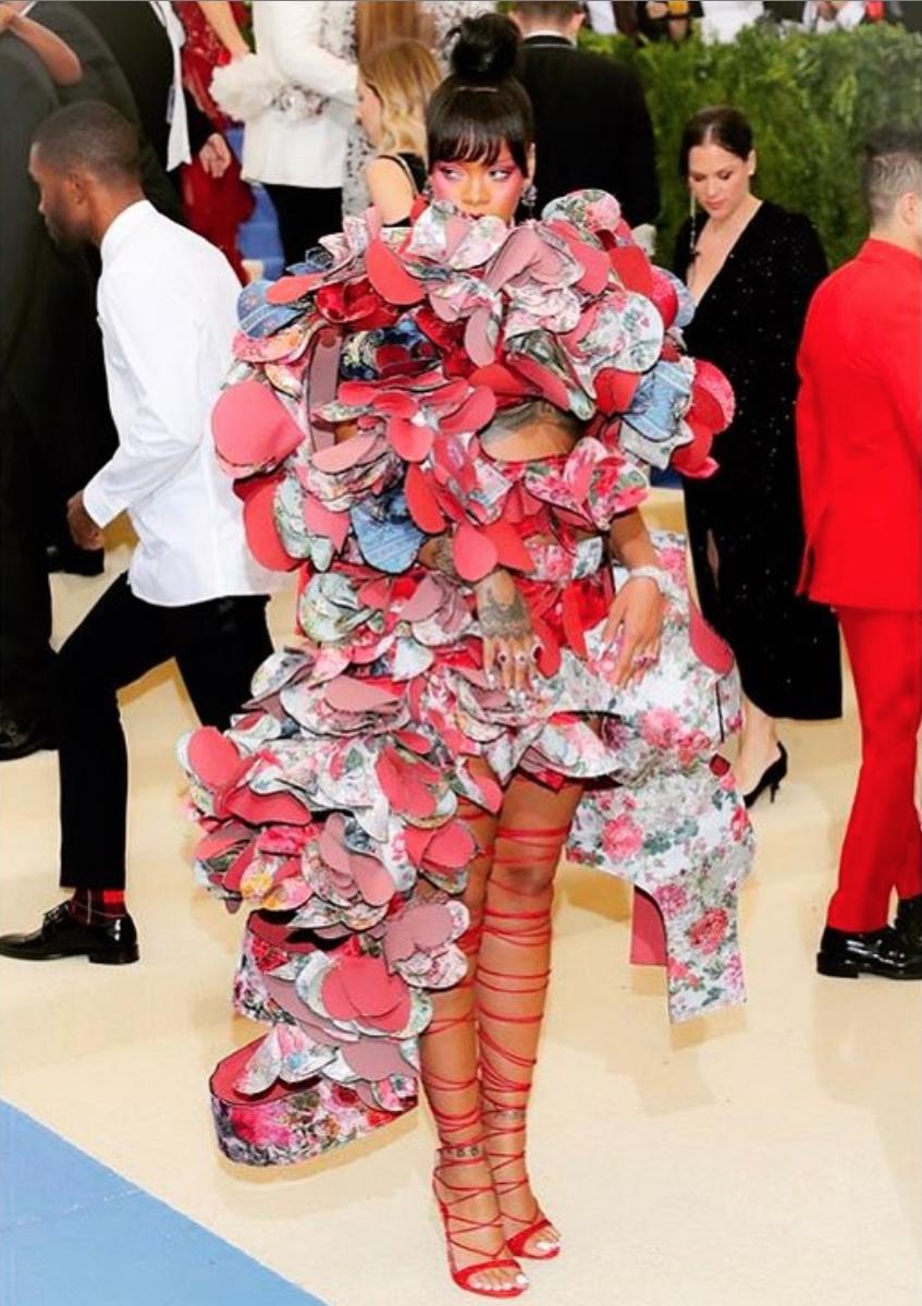 2017年のMETガラは、コムデギャルソンのデザイナー「川久保玲」がテーマ。顔が覆われてしまうほどの立体的なボリュームドレスを纏うリアーナの姿は、またもその年のSNSで最も騒がれたと言われるほど話題に。足元にはドレスと色でリンクしたストラップサンダルをセット。