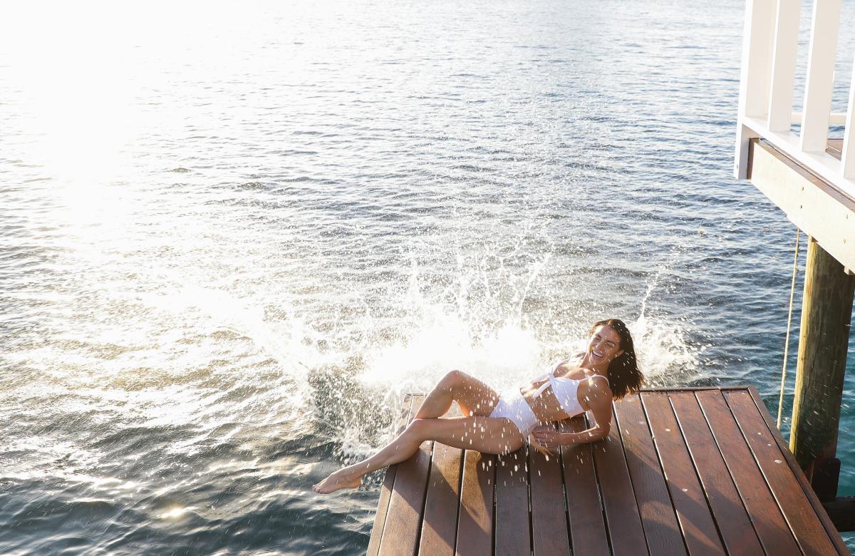 恋人が飛び込んだ際にできた、水しぶきを浴びているジェナ・ジョンソン(25)。彼女のように日焼けした肌に映えるホワイトのビキニは、アクセサリー次第で着こなしの幅が広がるので、ひとつあると重宝しそう。