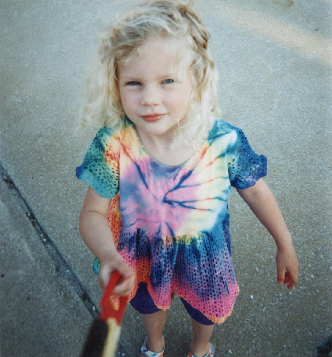 タイダイのワンピースを着たキュートな美少女は、5〜6歳ぐらいと思われる少女時代の人気歌手。カントリーシンガーになるため、14歳の時一家でテネシー州ナッシュビルに引っ越し、16歳でデビュー。当時からウェーブがかかったブロンドヘアの美少女カントリー歌手として注目されていた。