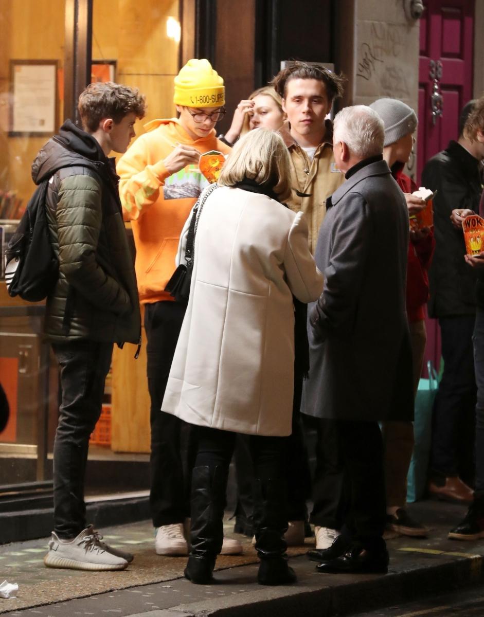 劇場前でキャッチされたブルックリンとニコラ。イエローのニット帽がロメオ。グレーのニット帽がクルス。ブルックリンの前に立つ後ろ姿の人物がヴィクトリアの両親。Photo:Backgrid UK/アフロ