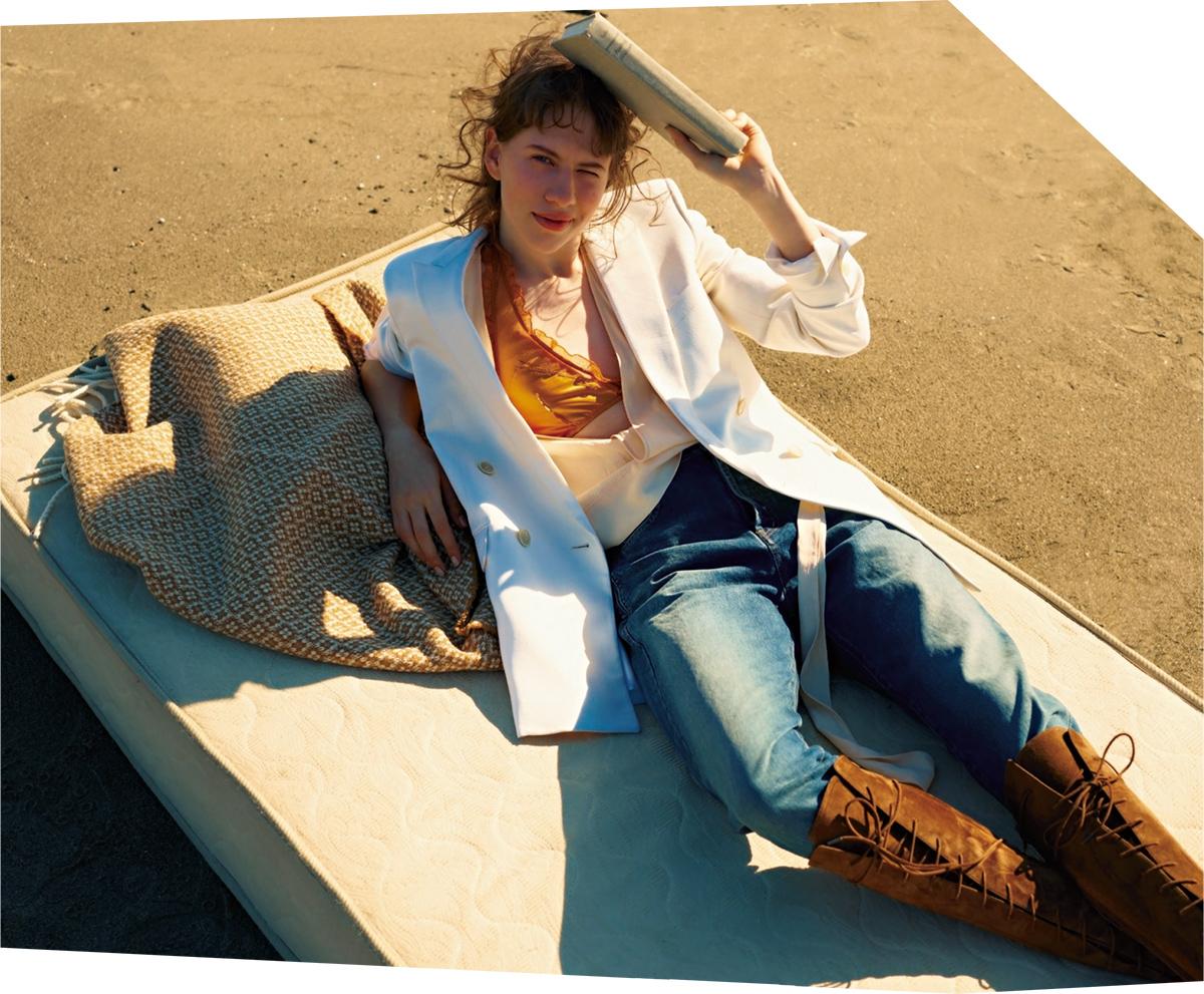 (モデル)ビアンカ・ジャガーが1970年代によくまとっていた白いスモーキングのセットアップを彷彿とさせる、ホワイトのジャケットに注目を。ダブルブレストで着丈が長く、ラフに袖をまくっても様になる。素材はハリのあるバージンウール。 ジャケット¥340,000・パンツ¥77,000・ブーツ¥200,000(参考価格)/サンローラン クライアントサービス(サンローラン バイ アンソニー・ヴァカレロ) ブラウス¥55,000/コロネット(フォルテ フォルテ) 中に着たチュールブラ¥26,000/アンダーカバー