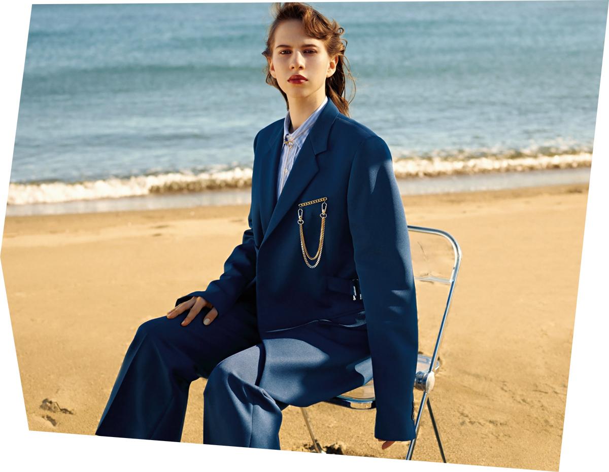 (モデル)50年代後半にロンドンで一世を風靡した「テディボーイ」スタイルのドレープジャケットがインスピレーション。ジャパニーズポリエステルで仕立てた細身かつ長めの着丈が特徴で、クロージャーにはボタンの代わりにベルトを配した。胸元のブローチを品のあるアクセントに。ジャケット¥210,000・パンツ¥75,000・ブローチ¥43,000・ネックレス¥45,000/メゾン マルジェラ トウキョウ(メゾン マルジェラ) シャツ¥16,000/レショップ 青山店(エルイー)