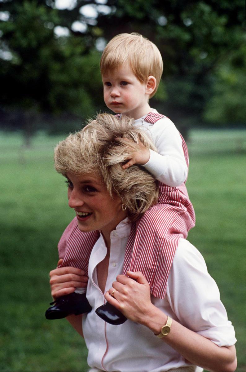 「ハイグローブ・ロイヤル・ガーデンズ」の広大な敷地で、外遊びを楽しむ母子。幼いハリー王子は肩車が怖いのか、母の頭をしっかりと掴む仕草が可愛らしい。(1986年) Photo : Getty Images