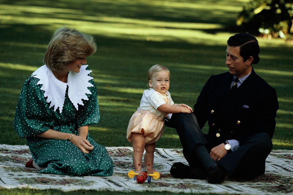 オフィシャルポートレート撮影会での、オフショット。父チャールズ皇太子のひざに手をつき、つかまり立ちをするウィリアム王子が愛らしさ満点。(1983年) Photo : Getty Images