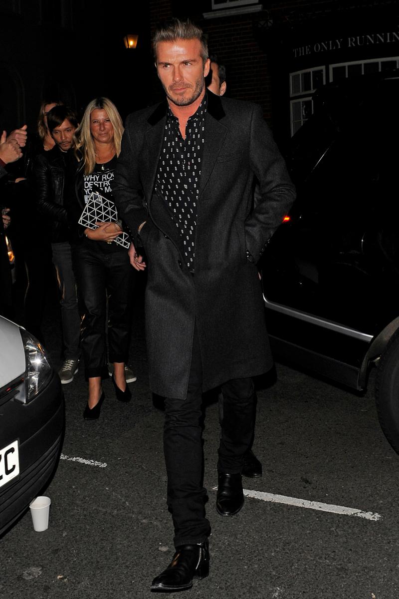 【2011〜2015年:ベッカムスタイル確立期】2014年11月、ロンドンでパーティに向かうデヴィッドをパパラッチ。柄のシャツにダークグレーのジャケットを合わせ、スリムなパンツで引き締め。文句なしのカッコよさに、世界中の女性がため息!