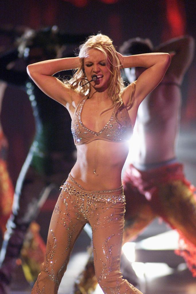セカンドアルバム『Oops!...I Did It Again』が全世界で2,000万枚を売り上げ、アイドルとして頂点を極めたブリトニー。ティーンにして億万長者となると、次に狙ったのは脱アイドル化。徐々に肌の露出が多くなり、セクシー路線へチェンジ。2000年の「MTVビデオ・ミュージック・アワード」のパフォーマンスでは、スーツ姿で登場するも途中で脱ぎ捨て、ジュエリーがちりばめられた下着風衣装に。18歳にして魅せた大胆なパフォーマンスと衣装で、世界中をあっと驚かせた。