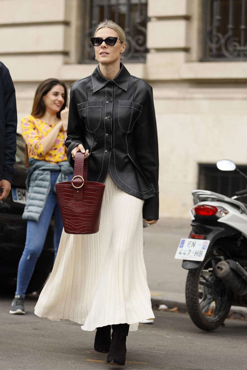 白いプリーツスカートで、レザーシャツをフェミニンに