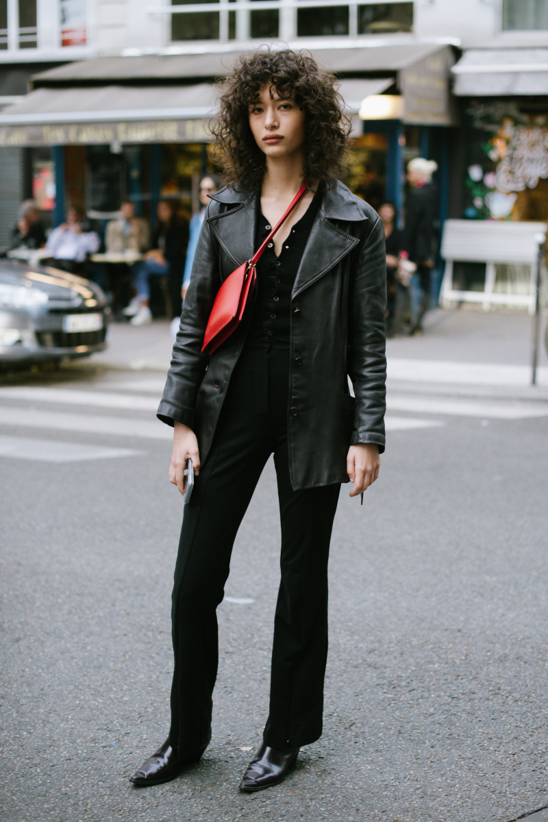 オールブラックスタイルのアクセントに、赤いバッグを