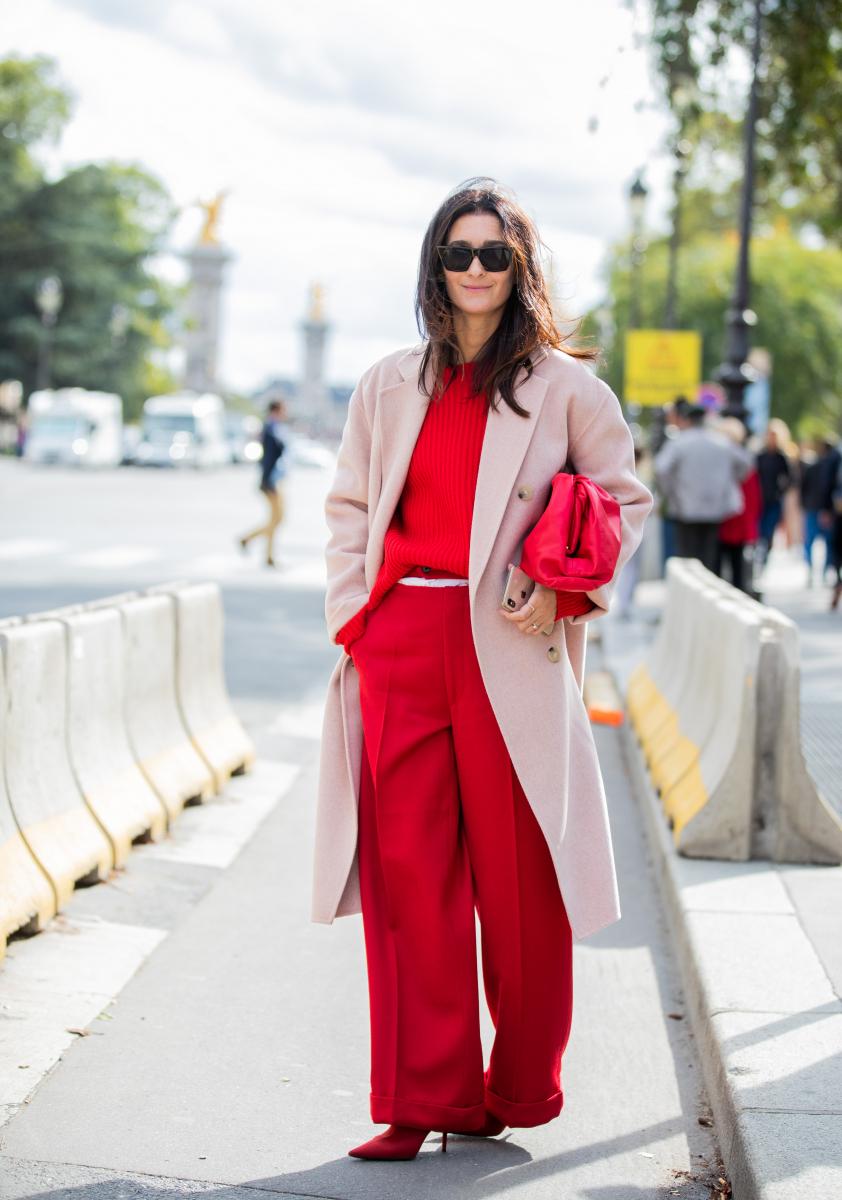 オールレッドのスタイリングに優しいピンクのコートを