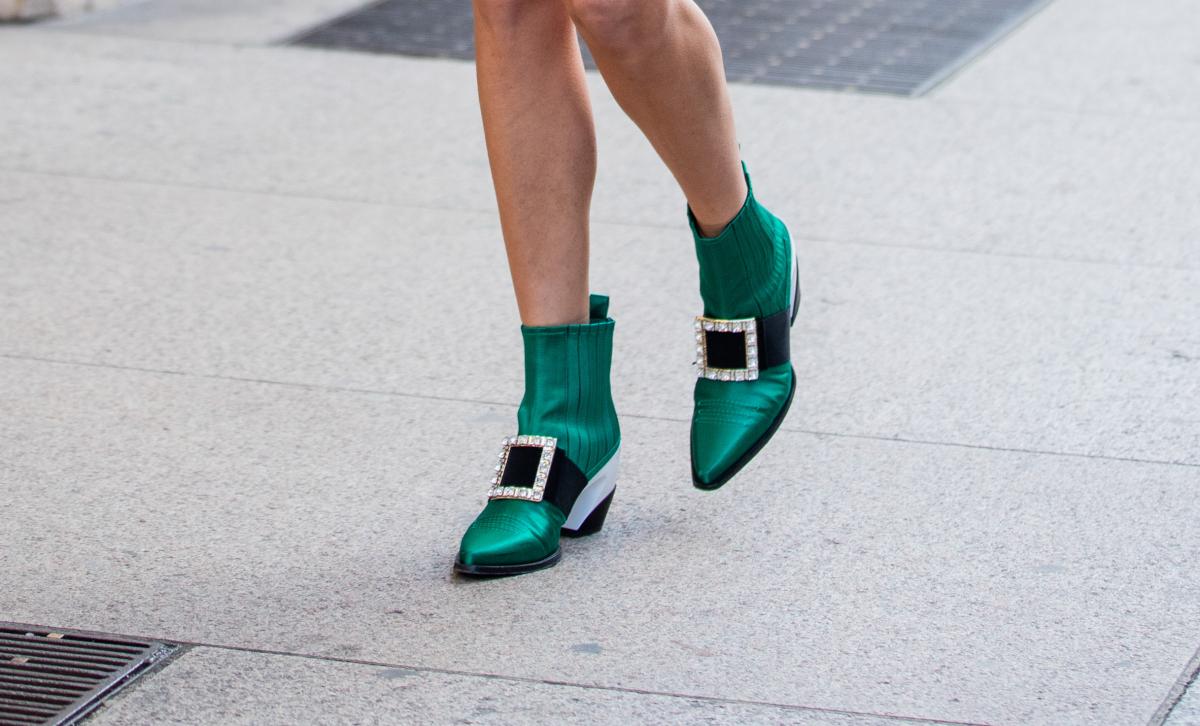 セットアップの足もとはメタリックグリーンのブーツ