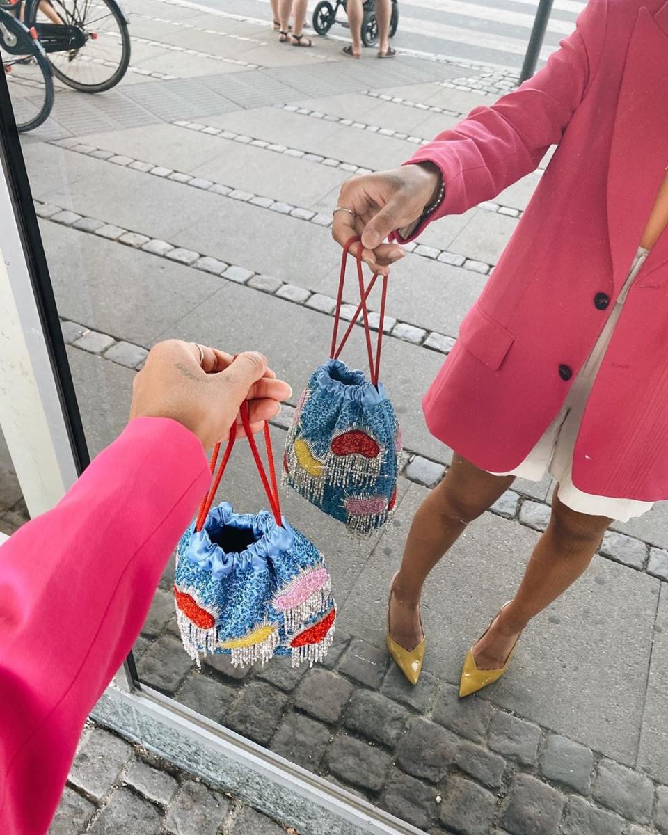 ピンクのジャケットにはプレイフルな巾着バッグを