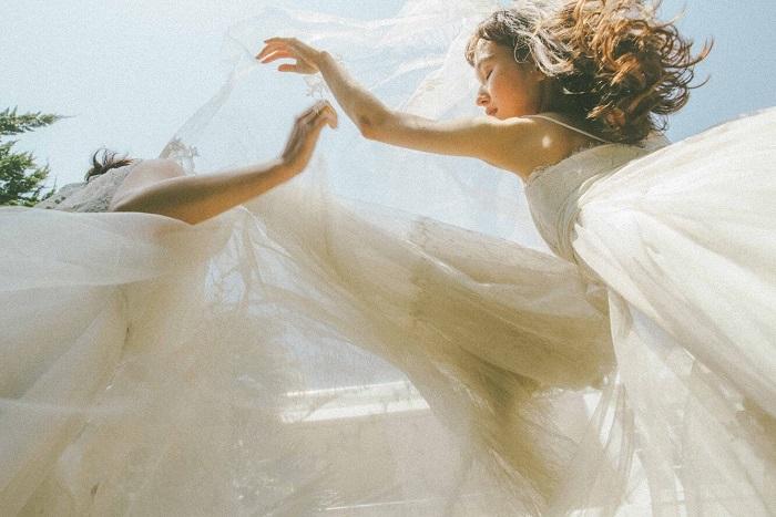 チュールやレースなど、繊細なシアー素材を駆使したドレスは開放的なロケーションにもマッチ。ドレス¥###,###~(販売・レンタル)