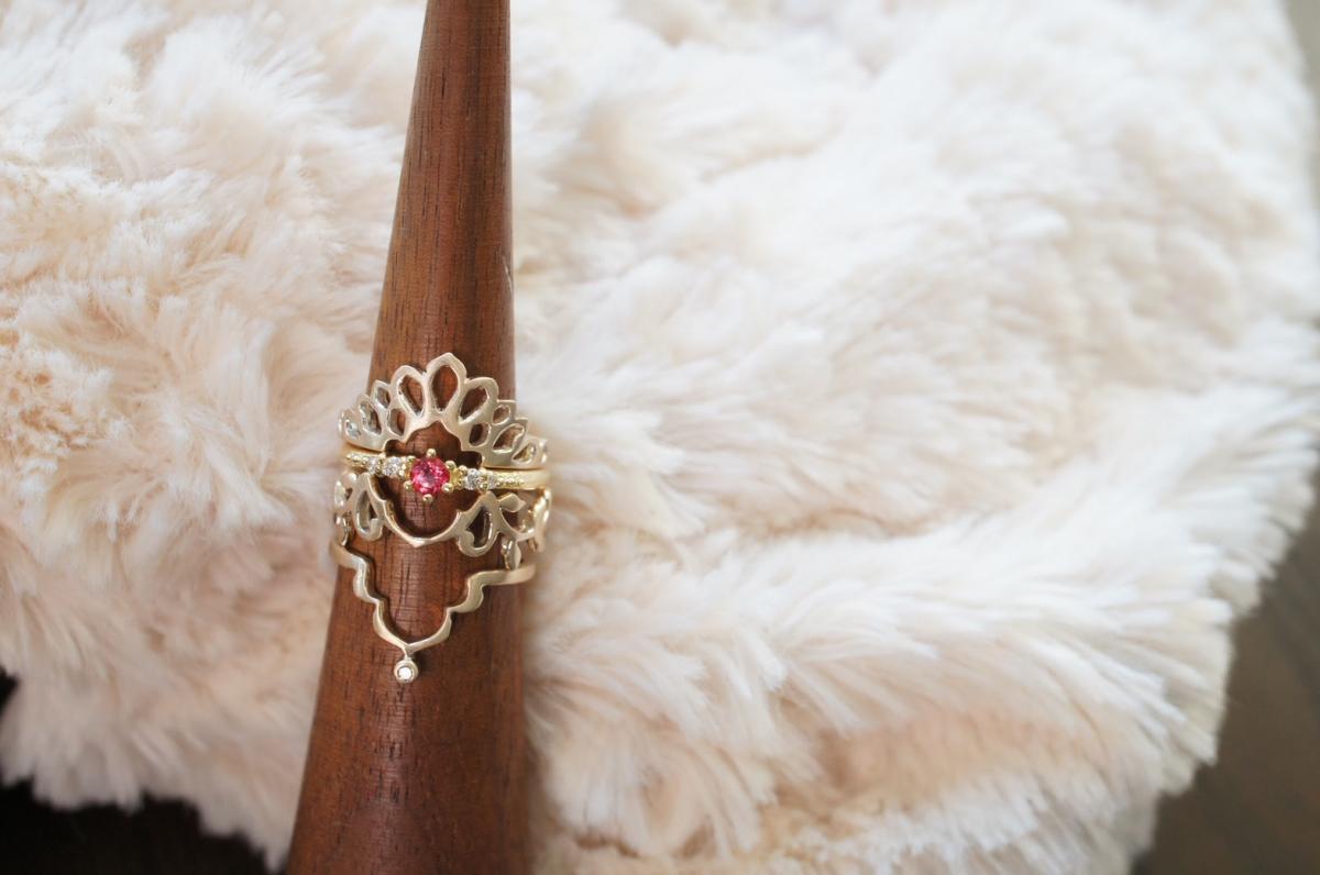 ミャンマー産のピンクスピネリを使ったリング(¥115,560)を中心に、クジャクを模したピーコックリングや、イバラモチーフのリング、タージマハルに着想したリングなど、重ねづけを楽しめるのも特徴。指の上に模様を描くようなデザインが秀逸!