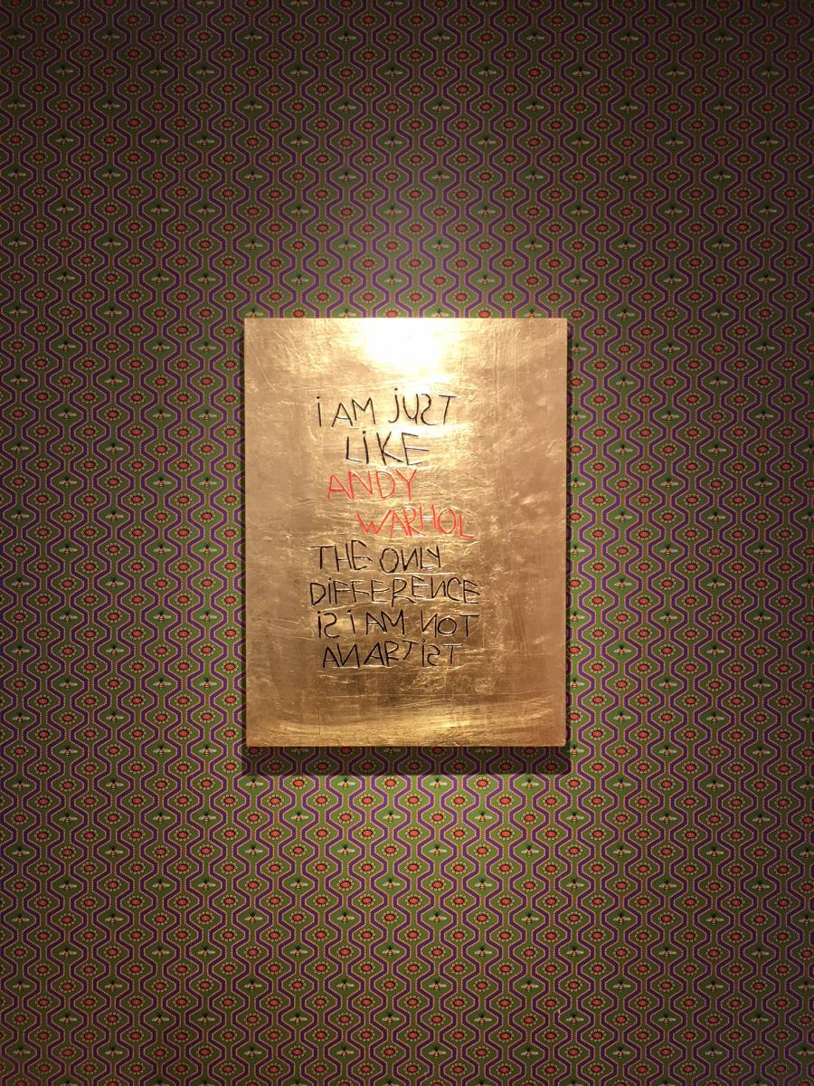 ゴールドの板に描かれた手書きメッセージ。確かにこの展示は、アンディ・ウォーホルに通ずる消費社会への批判を思わせます。