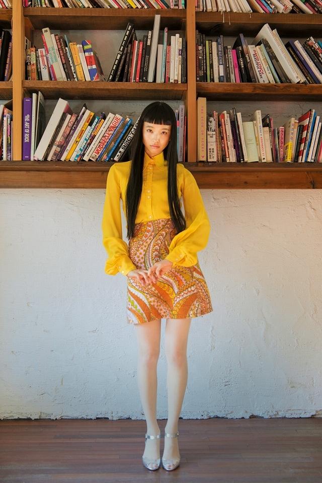 トレンドカラーのイエローのブラウスとサイケ柄のスカート。70年代ファッションが今また新鮮